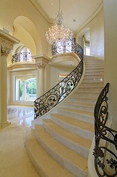 Love the flowing curve of the beautiful stair- case and the many other outstanding details going on in this foyer.
