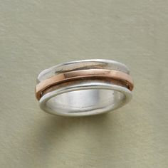 CIRCUMNAVIGATION RING--Handmade using the age-old lost wax casting technique, a sterling silver ring holds a slender spinner of 14kt rose gold. USA. Whole sizes 5 to 9. This ring is licensed under U.S. Patent Nos. 6,497,117.