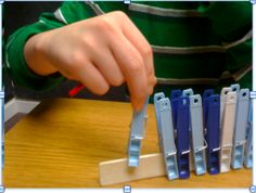 """Use the thumb, index & middle fingers to squeeze pegs & place them on a ruler or paint stirrer ("""",)"""