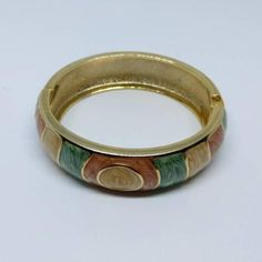 Vintage bangle, 1980s costume, enamel bangle with goldtone detailing.  Almost perfect condition, with minimal signs of wear on gold.  *We aim to sell items in the best possible condition, however most of our stock is vintage and therefore secondhand and may have some signs of wear. Any major flaws will be noted in description and highlighted in photos to the best of our ability*