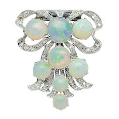 Opal, Diamond and Platinum Clip Brooch, circa 1930 Fashioned as a ribbon bow with flaring tails set with old mine-cut diamonds and decorated with round opals, mounted in platinum
