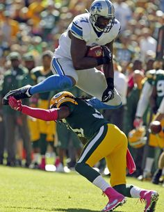 Detroit Lions' Brandon Pettigrew leaps over Green Bay Packers' Davon House after a catch.
