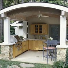 Freestanding kitchen    The lovely arched roof on this outdoor kitchen provides protection from the elements, and a place for a ceiling fan and lighting. There's room inside for a bar-height table for two, and doors in the back lead to a patio with more seating. The cement floor has a drain in the middle.    Add your comment