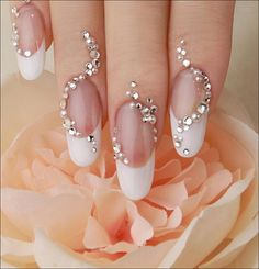 This gorgeous nail art is created with a vertically curved line of rhinestones and pearls combined with a white french manicure. This style can be perfect for brides.