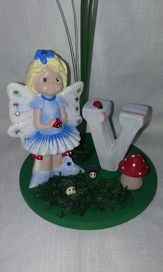"""FAIRYLAND Alphabet """"V""""        Fairy Stands Approximately 12  cm tall base of fairy land 15 cm wide    Placed in the wings and center of the flowers are the Finest Austrian Crystals     Please Select your option as to witch fairy you would like ( 3 to choose from)    Iris - Fairy with Wand  Daisy - Fairy with Lady Bug  Aster -  Fairy Sitting    These Little Fairy Lands have 2 little rabbits or Hedgehogs accompanying ( chosen as random. color of fairy is also random)     IF YOU WOULD LIKE A…"""