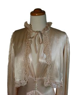 """Late 1930s Early 1940s Silk PEIGNOIR SET. Charmeuse silk and lace vintage bed jacket and nightgown. Peachy pink Hollywood Glamor.    BED JACKET:  ~Beautiful scalloped lace trims collar, front plackets, hem and sleeves.  ~Front tie at rounded lace neckline  ~Sleeves are gathered at shoulders and bell to a glamorous 20"""" circumference at lace edge.    NIGHTGOWN: ~Fabric has incredible fluidity! ~Fitted bodice with small cap sleeves  ~Low neckline with under bust seam and matching seam below…"""