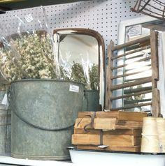 Old zinc bucket to hold larkspur, mirrors from old vanity, antique books with ragged edges. A French Apartment stall at A Antique Mall.