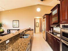 Me encanta esta cocina. Es moderna, con amplios gabinetes y puertas en caoba, topes de granito y tiene una amplia isla.