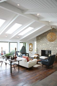 Living room, skylights, rough hewn wood floors, stone fireplace. Mid-century modern, eclectic furnishings.
