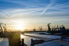 Zonsondergang in de Waalhaven in Rotterdam met op de achtergrond de diverse kranen en binnenvaartschepen