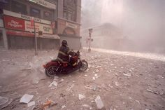 Firefighter Tim Duffy arrives downtown on his Harley after first tower collapse, 9/11/2001. Photo by Allan Tannenbaum
