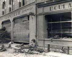 """Soldier taking a well-earned nap on street in Marigny, France. Street signs: """"Paille Graineterie Semences."""" """"Boulangerie."""""""