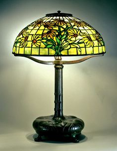 Reading lamp, c. 1910. Shade No. 1447, black-eyed Susan design, dome shape; Standard No. 357, leaf design, cushion base leaded glass and bronze; Tiffany Studios, New York City, 1902–32; H. 22 in., diam. 16 in. (70-028).