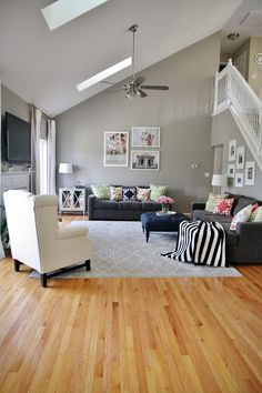 Gray living room with pops of pattern and color.  Gray walls and sofas, gray area rug, light hardwood floors