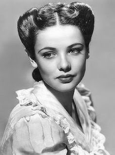 1940s. Hair rolled to the back, with a center part. Hair probably tucked up in back with a barrette.