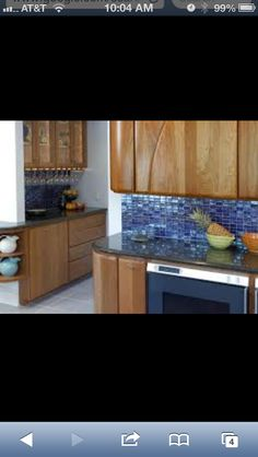 Blue tile backsplash with oak cabinets. Something like this would go with the flooring and could help the the kitchen and living room together.