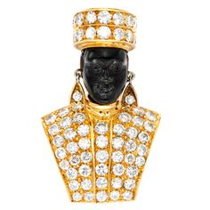 An 18kt gold and diamond blackamoor brooch, the pave set diamond torso and turban with a carved ebony face