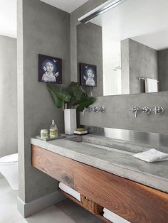Natural concrete countertops make an interestingly imperfect statement that balances sleek furnishings. This mottled, slightly pitted concrete countertop supplies a fetching surface for a stained floating vanity, stainless-steel backsplash, and polished chrome faucets./