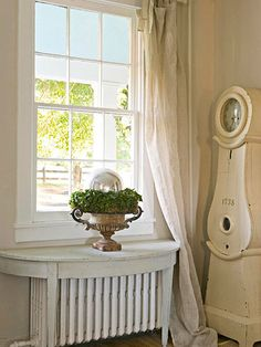 White on White: White walls create a neutral backdrop that lets your furnishings and accents shine. Linen curtains casually drape the front window and drag on the floor. A demilune table with a distressed white finish sits over the radiator. French Decor, French Country Decorating, Country French, Swedish Decor, Swedish Style, French Farmhouse, Radiator Shelf, Radiator Ideas, Diy Radiator Cover