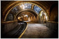 """The Interborough Rapid Transit (IRT) opened this """"Romanesque Revival jewel of a station below City Hall"""" in 1904. (It closed in 1945.) """"City Hall Station features skylights, colored glass tiles, brass chandeliers and arched tile work, named after the station's designer Rafael Guastavino, that can also be seen in the dining level of Grand Central Station- particularly in the Oyster Bar."""" Caption from link"""