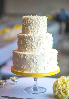 Cake by Layers Cakes Inc. in Halifax, Nova Scotia. From the designer: This white-on-white wedding cake design with sugar petal flowers cascading over tiers and subtle hints of yellow was inspired by summer. Photography by Cooked Photography .