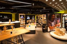 The image of the store is boldly simple, featuring a dramatic patterned lighting system, and bleached wood cabinets surrounded by a happy spring green perimeter wall. Retail Store Design, Retail Shop, Visual Merchandising, Electrical Stores, Showroom Interior Design, Retail Solutions, Bleached Wood, Electronic Shop, Conceptual Design