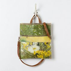 Daisy Bouquet Vintage Painting Bag  $398.00 Artist and designer Leslie Oschmann scours markets all over Holland and Belgium, searching for the quirky secondhand paintings that compose her handmade bags. Finished with natural leather handles and fitted with a zip front pocket, Oschmann repurposed these works of art especially for terrain, featuring picturesque moments from the idyllic Dutch countryside.