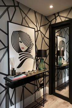 """""""The entrance hallway is always a talking point, the large monochrome print wallpaper packs a punch and the artwork works just perfectly to inject a pop of colour."""" The wallpaper is by Harlequin (Sumi)."""
