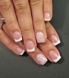 Wonderful French tips over a nude nail polish design. Let your nude nails stand out by adding cute flower embellishments on top.