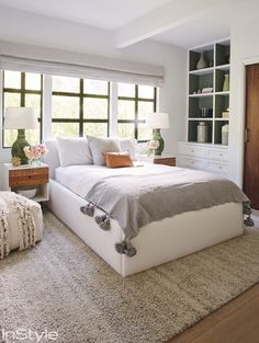 Lea Michele's bright bedroom with white bedding, a large rug, and a leather throw pillow