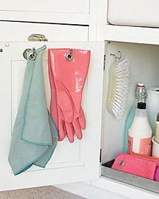 Don't let kitchen rags and dishwashing gloves clutter the sink area. Instead, hang them from hooks screwed to the inside of a cabinet door, where the items can stay out of sight as they dry. A grommet-setting kit lets you make tear-proof holes in cloth, rubber, and other soft materials.