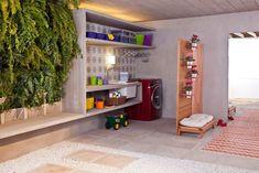 lavanderia na garagem com um biombo para separar e ao lado jardim vertical com samambaias