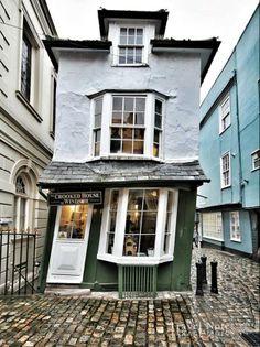 """The Crooked House of Windsor.  Crooked House, ovvero """"la Casa Storta"""", edificio, costruito nel 1592, che ai passanti sembra essere sempre sul punto di crollare. La casa ha infatti una particolare inclinazione su un lato, dovuta ad un errore commesso durante una ristrutturazione nel '700, ovvero all'uso di quercia verde non stagionata. Un errore di valutazione che ha garantito tuttavia a quel piccolo edificio tutta la notorietà che altrimenti non avrebbe avuto."""