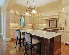 Cream kitchen cabinets, darker wood island, lighter toned wood floors
