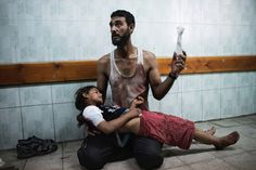 Jul. 20, 2014. A Palestinian man holds a girl injured during shelling at a U.N.-run school sheltering Palestinians, at a hospital in the northern Gaza Strip.