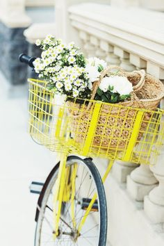 A yellow bike with a basked full of flowers - perfect for any lady