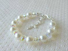 A beautiful bracelet featuring white Swarovski pearls, sparkling Swarovski crystals, and sterling silver. It is finished with a lobster clasp and a cross charm. It is a perfect gift for baby girls, flower girls, christening, baptism or first communion, blessing, shower gift, Christmas and birthday. Material : • Ÿwhite Swarovski Pearls and crystals • Ÿ925 Sterling silver ( including the cross charm, child size lobster clasp, cover beads, jump rings and wire protectors) • Professional beading…