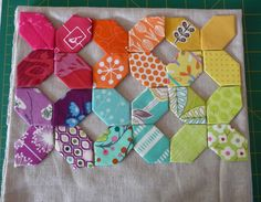 A very quick mock up of my latest idea. Linen background and paper pieced shapes in rainbow colours.  Will probably add stitching. It will most likely finish at approx  11 inches by 8 inches  and be flat.