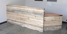 Maybe line front of cash wrap with pallet wood? Reclaimed wood reception desk or retail cash wrap. $6,000.00, via Etsy.