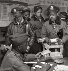 """Suicide Rations:  March 1945. """"Tuskegee Airmen 'Escape kits' (cyanide) being distributed to fighter pilots at air base in Ramitelli, Italy."""" Theodore G. Lumpkin Jr., seated, with (L-R): Joseph L. """"Joe"""" Chineworth, Memphis, Class 44-E; Robert C. Robinson, Asheville, Class 44-G; Driskell B. Ponder, Chicago, 43-I; Robert W. Williams, Ottumwa, Iowa, 44-E. (Gelatin silver print by Toni Frissell.)"""