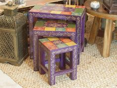 Large: 46cm high x 46cm wide x 30cm deep.  Medium: 38cm high x 35.5cm wide x 26cm deep.  Small: 30cm high x 25.5cm wide x 22cm deep.  Purple and mixed colours. Each set will vary from the ones pictured.  3 very colourful hand painted wooden tables. Beautiful detailing applied to the top of them.   To clean, just wipe with a damp cloth.  Handcrafted in Rajasthan, India.