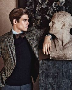 The elite look - cable knit sweater, flannel trousers, blue-green-brown checked sport coat, burgundy bow tie with polka dots, some old Roman statue to add an intellectual finishing touch