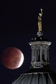 """The eclipse appears behind John Gelert's """"Enlightenment Giving Power"""" statue, which sits on top of the dome of the Bergen County Courthouse in Hackensack, New Jersey. 