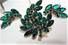 Item # 021711  An amazing unsigned,circa 1950s-60s, emerald green glass rhinestone brooch and matching clip on earrings demi parure set. Brooch consists of 17 emerald green glass navettes and 10 small rounds, all closed back hand prong set in a gold tone rhodium plating. Brooch is in the classical figural leaf design.  Each earring consists of 4 emerald green glass navettes, 1 medium round and 5 small rounds. They are all hand prong set with the rounds being closed back and the navettes are…