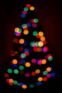 A beautifully bokeh'd out Christmas tree in a dimly lit room.