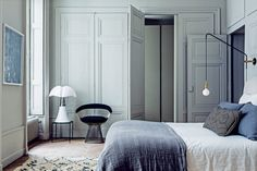 Minimalist bedroom with gray hues, a hanging pendant sconce and a modern armchair