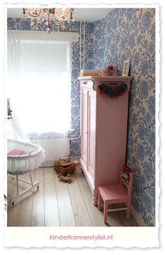 beautiful girl's nursery with blue wallpaper and pink furniture
