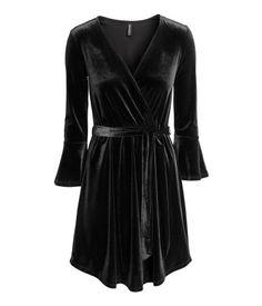 Musta. Lyhyt mekko pehmeää ja kiiltävää veluuria. V-pääntie, jossa kiinteä kietaisuosa. 3/4-hihat, joissa trumpettisuut. Joustava vyötäröleikkaus, jossa