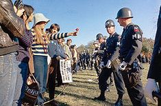A hippie holds out a flower to National Guard Members during protests against the Vietnam War.