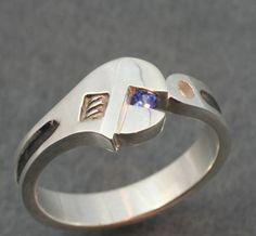 Fotografía de anillo en forma de llave inglesa sosteniendo un zafiro de color azul